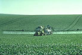Tractor spraying pesticides in field.