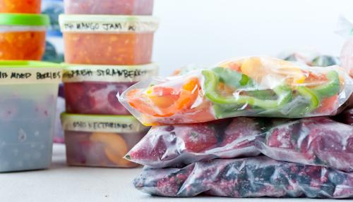 Containers and ziplock bags of frozen fruits and vegetables.